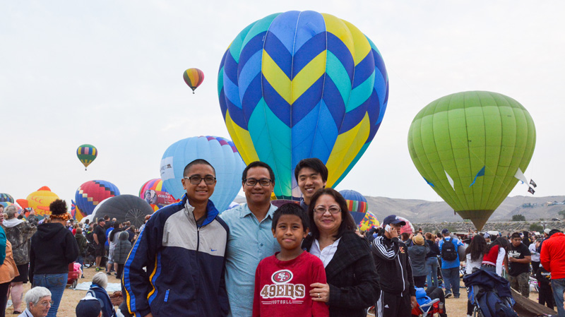 j-1 high school exchange student with host family in front of balloon